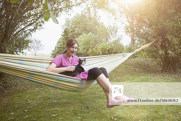 Entspannte Frau mit Katze in der Hängematte
