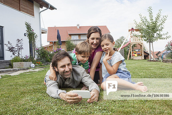 Smiling family of four in garden with cell phone