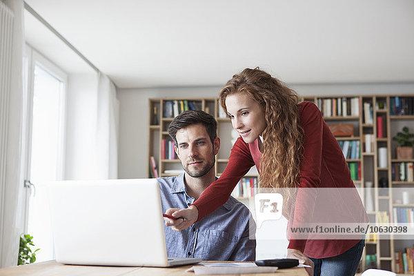 Paar zu Hause mit Blick auf den Laptop