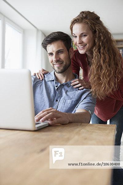 Lächelndes Paar zu Hause beim Betrachten des Laptops