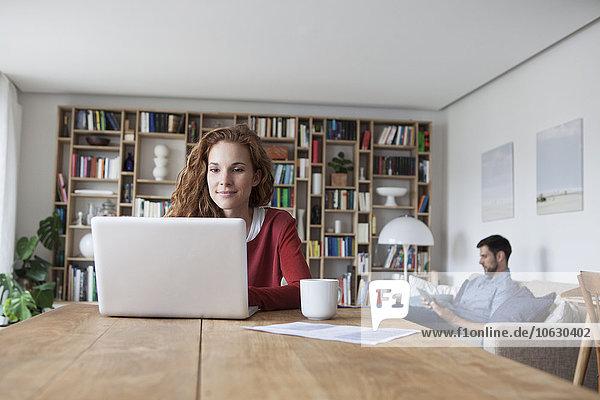 Frau zu Hause mit Laptop und Mann im Hintergrund
