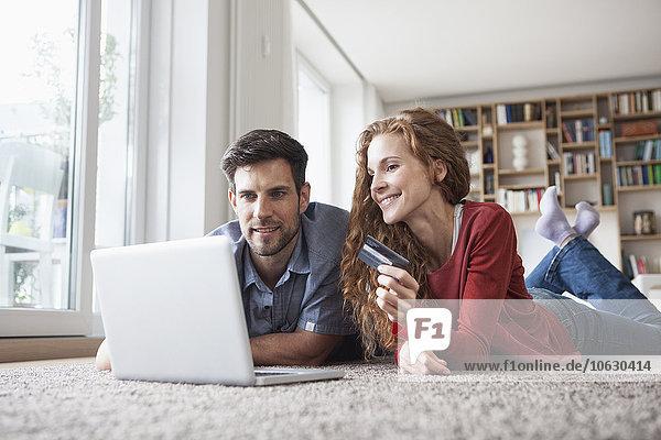 Glückliches Paar auf dem Boden liegend online einkaufen