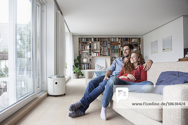 Relaxed couple at home on couch looking out of window