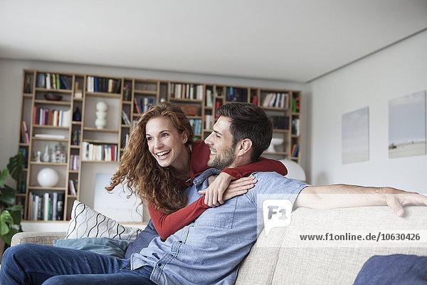 Fröhliche Frau umarmt Mann auf Couch