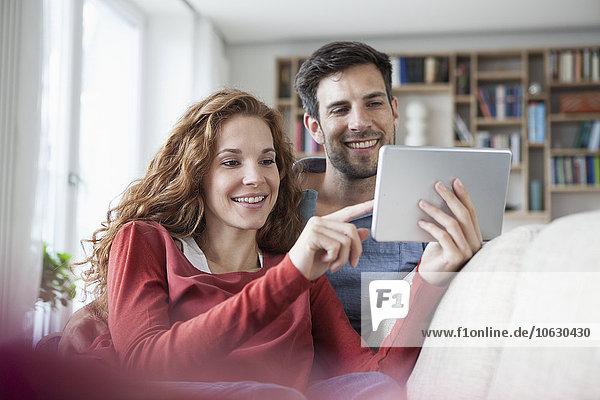 Entspanntes Paar zu Hause auf der Couch mit digitalem Tablett