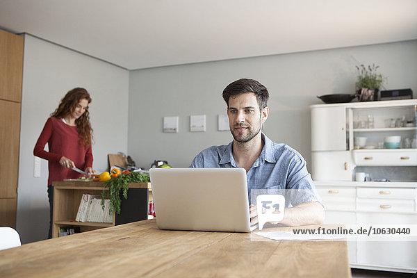 Mann zu Hause mit Laptop und Frau im Hintergrund Gemüse schneiden
