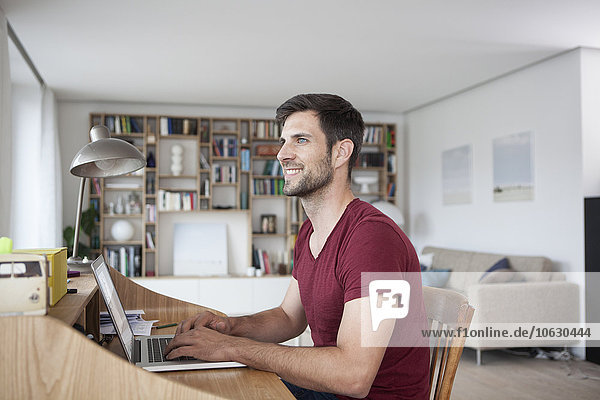 Smiling man at home using laptop