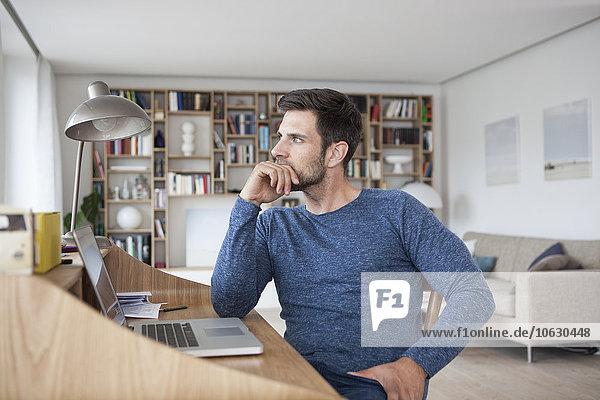 Mann zu Hause schaut weg vom Laptop