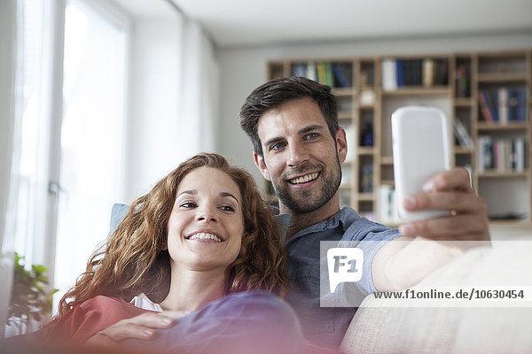 Entspanntes Paar zu Hause auf der Couch mit Blick aufs Handy