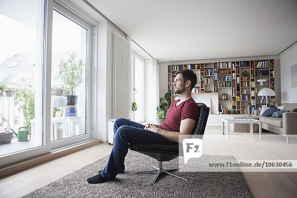 Man at home sitting in armchair looking out of window