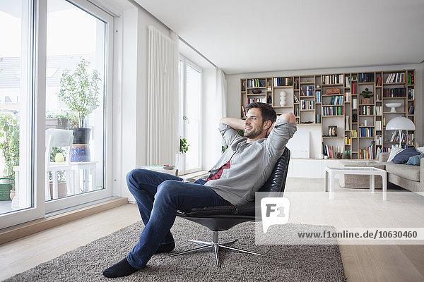 Lächelnder Mann zu Hause im Sessel sitzend mit den Händen hinter dem Kopf
