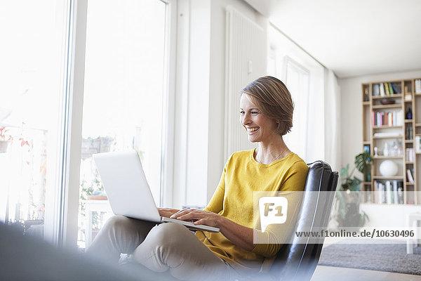 Glückliche Frau zu Hause sitzend auf Lederstuhl mit Laptop