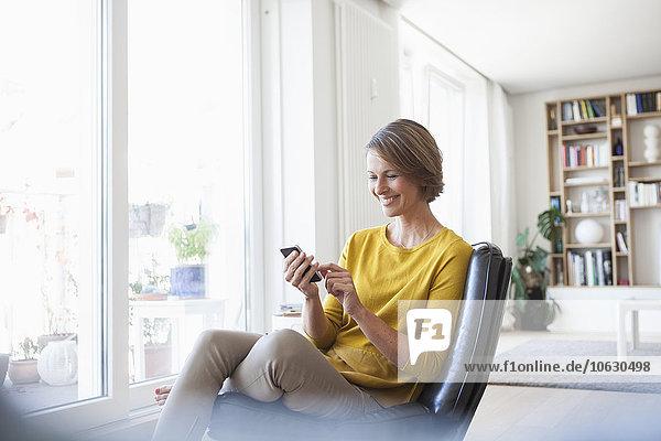 Entspannte Frau zu Hause sitzend auf Lederstuhl mit Handy