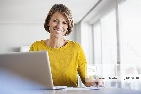 Porträt einer lächelnden Frau zu Hause mit Laptop