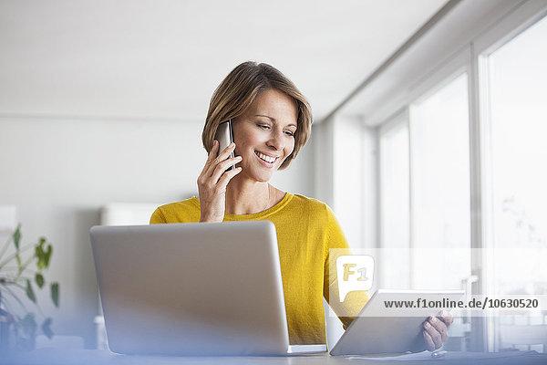 Lächelnde Frau zu Hause mit Laptop  digitalem Tablett und Handy