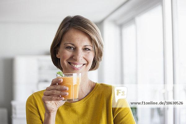 Porträt einer lächelnden Frau mit einem Smoothie