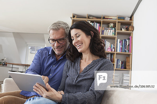 Lächelndes Paar zu Hause auf der Couch mit digitalem Tablett