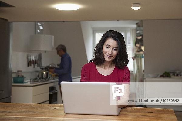 Lächelnde Frau zu Hause mit Laptop mit Mann im Hintergrund