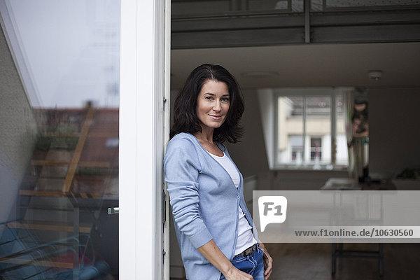 Porträt einer lächelnden Frau  die sich gegen die Balkontür lehnt.