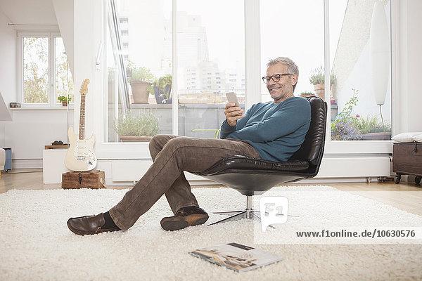 Lächelnder  reifer Mann zu Hause auf dem Stuhl sitzend und auf das Handy schauend.