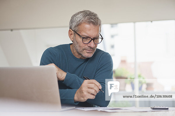 Mature man at home using laptop