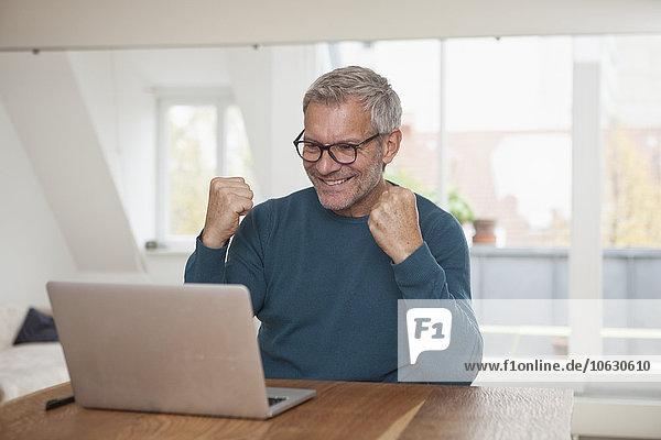 Älterer Mann zu Hause mit Blick auf Laptop-Jubel