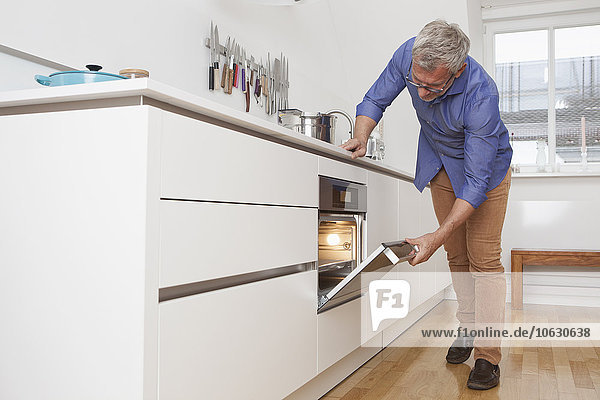 Mature man in kitchen opening oven