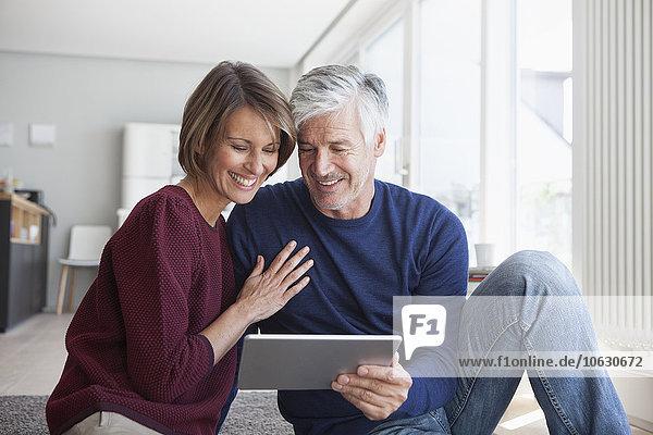 Lächelndes Paar sitzt zu Hause auf dem Boden und schaut auf ein digitales Tablett.