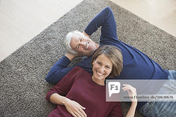 Ein glückliches Paar entspannt sich gemeinsam auf dem Teppich