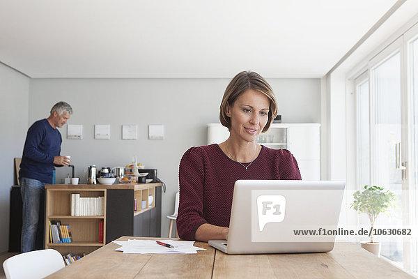 Porträt der Frau  die den Laptop zu Hause benutzt