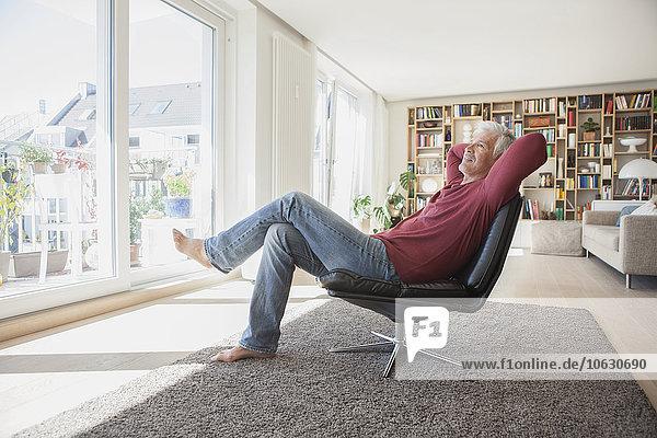 Mann entspannt auf Lederstuhl zu Hause