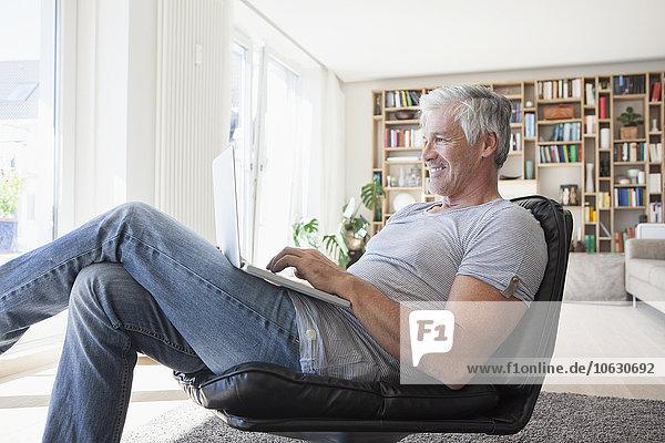 Lächelnder Mann entspannt auf Lederstuhl zu Hause mit Laptop
