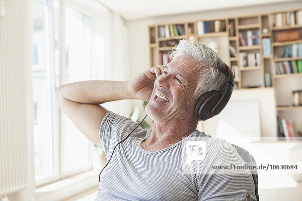Porträt eines entspannten Mannes  der zu Hause Musik mit Kopfhörern hört.