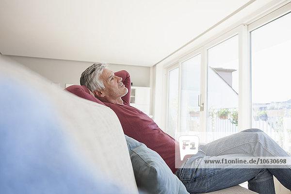 Nachdenklicher Mann sitzt zu Hause auf der Couch.