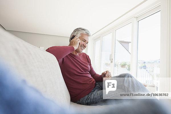 Lächelnder Mann sitzt zu Hause auf der Couch und telefoniert mit dem Smartphone.