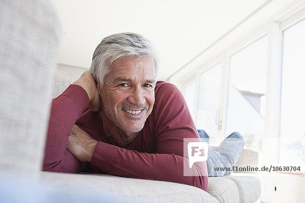 Porträt eines lächelnden reifen Mannes mit grauen Haaren und Stoppeln auf der Couch zu Hause.