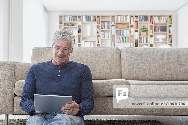 Lächelnder Mann sitzt zu Hause vor der Couch und benutzt ein digitales Tablett.