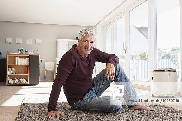 Porträt eines reifen Mannes  der zu Hause auf dem Boden sitzt.