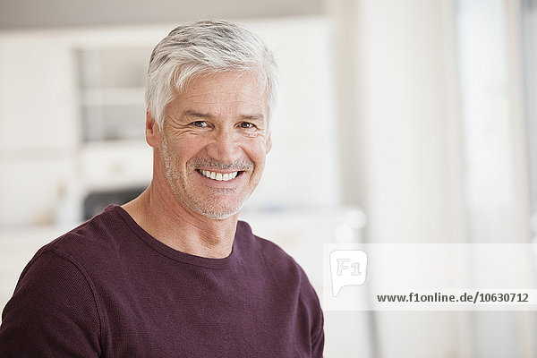Porträt eines lächelnden reifen Mannes mit grauen Haaren und Stoppeln