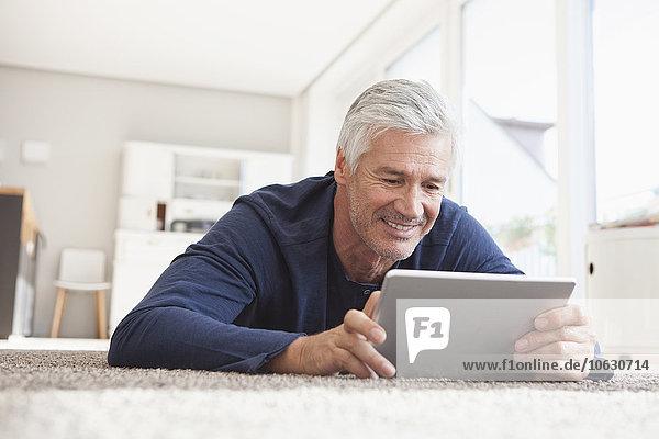 Lächelnder Mann zu Hause auf dem Boden liegend mit digitalem Tablett