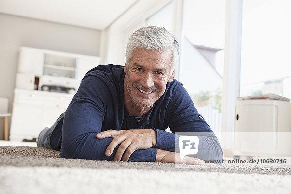 Porträt eines lächelnden Mannes,  der zu Hause auf dem Boden liegt.