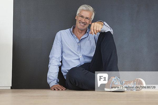 Porträt eines lächelnden reifen Mannes  der auf dem Boden vor einer grauen Wand sitzt