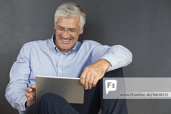 Lächelnder reifer Mann auf dem Boden sitzend mit digitalem Tablett