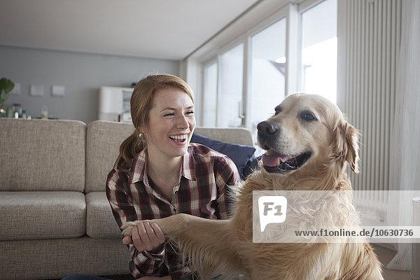 Porträt der lächelnden jungen Frau mit der Pfote ihres Hundes