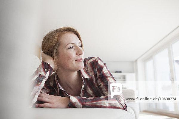 Lächelnde junge Frau entspannt auf der Couch