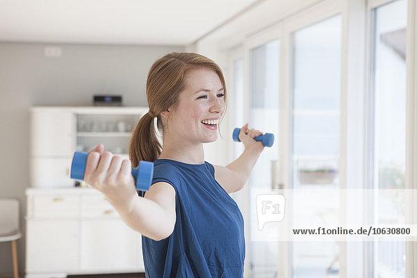Porträt einer lächelnden jungen Frau  die zu Hause mit Hanteln trainiert.