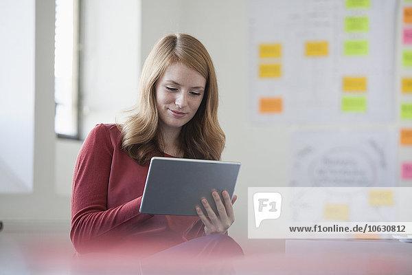 Junge Frau im Amt mit digitalem Tablett