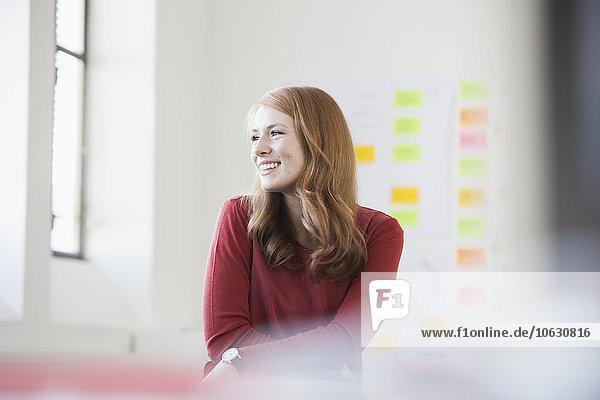 Junge Frau im Büro lächelt glücklich