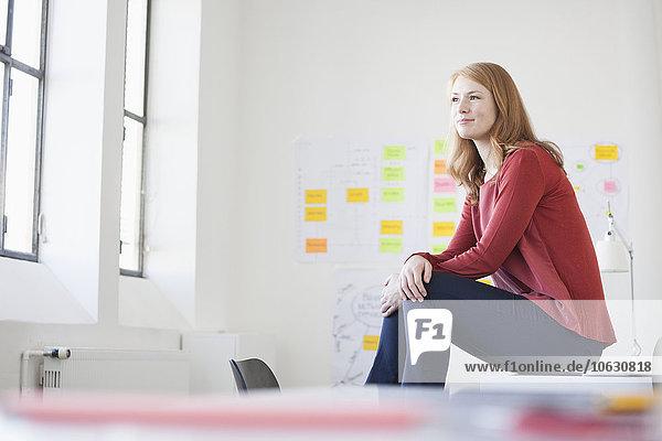 Junge Frau im Büro auf dem Schreibtisch sitzend  nachdenkend