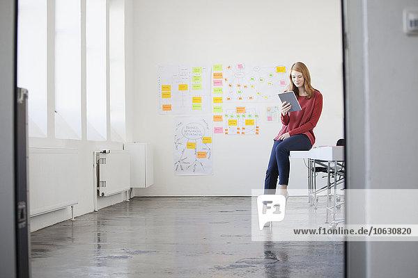 Junge Frau im Büro sitzend auf dem Schreibtisch mit digitalem Tablett